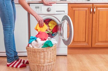 Mujer joven carga la ropa en la lavadora desde el cesto de la ropa antes de lavar.