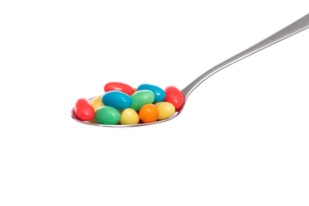 Multi-colored candies in a spoon on white background.