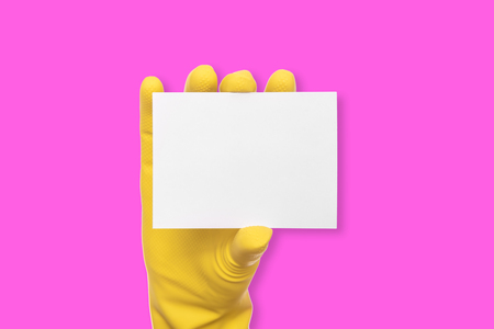 A rubber-gloved hand holds a white blank business card on pink background.