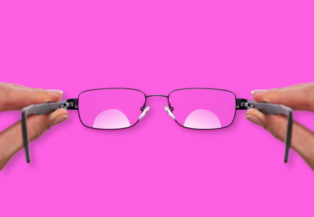 Glasses in a female hand on pink background. 스톡 콘텐츠