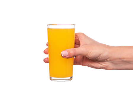 Female hand holding a glass with orange or citrus juice on white background.