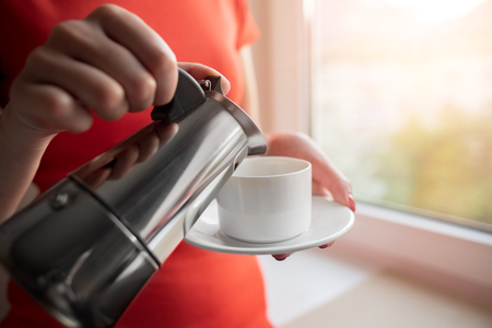 A woman pours coffee into a cup from a coffee maker.