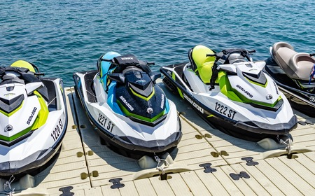Water motorcycles are parked on the dock.
