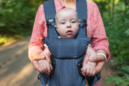 Young mother and her baby girl in a baby carrier.
