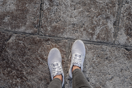 Womens legs in white sneakers on the pavement.