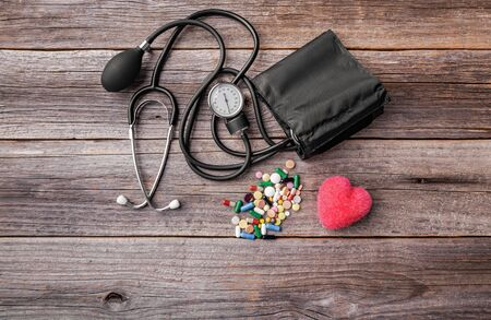 Tonometer pills and heart model on a wooden background. 스톡 콘텐츠