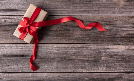 A box with a gift tied with a red ribbon on wooden background. 스톡 콘텐츠