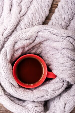 A winter scarf on wooden table wraps a cup of tea or coffee.