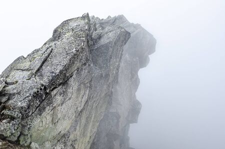 Top of the rocky mountain is shrouded in thick fog. Stock Photo