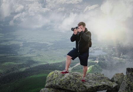 A photographer on top of a steep cliff and skyline in high mountains. Stock Photo