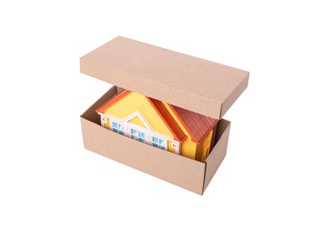 Toy model of a house in a cardboard box on white background.