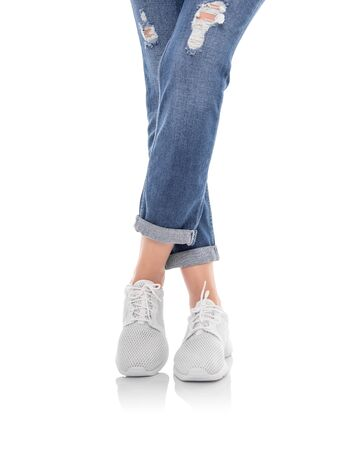 Legs in jeans and white sneakers isolated on a white background.