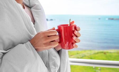 Girl wrapped in a blanket on the balcony in the morning drinks coffee or tea.