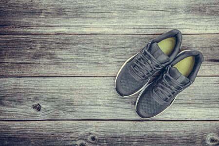 Black sneakers on a wooden background.