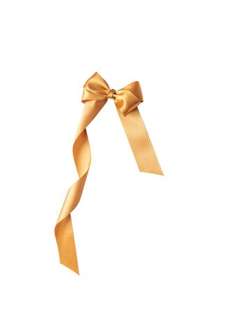 A golden ribbon with a bow on a white. 写真素材