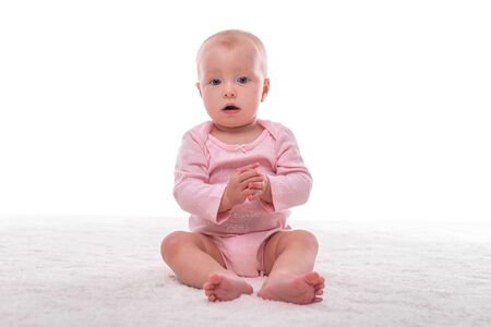 Small baby girl on a white carpet in a light room. Foto de archivo - 132120483
