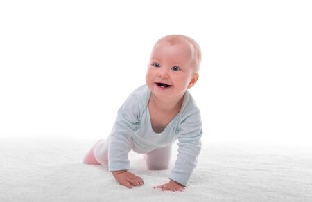 Small baby girl on a white carpet in a light room. Foto de archivo - 132120467