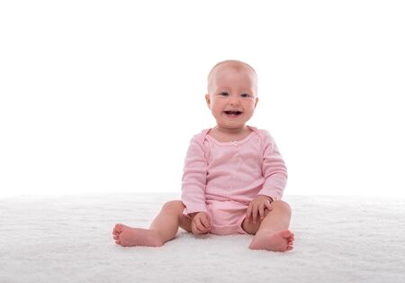 Small baby girl on a white carpet in a light room. Foto de archivo - 132120336