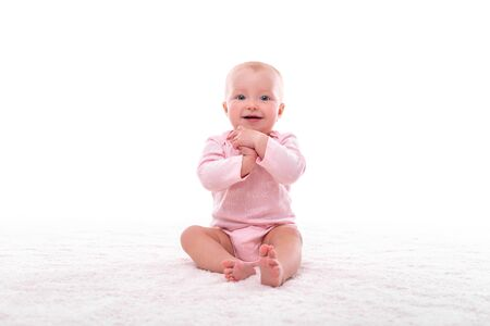 Small baby girl on a white carpet in a light room. Foto de archivo - 132121391