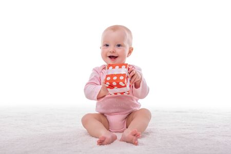 Little baby girl and a box with a gift on a white.