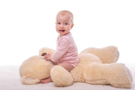 Little girl and a plush bear on a white background.