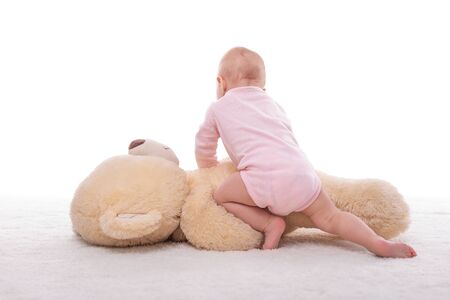 Little girl and a plush bear on a white background. Zdjęcie Seryjne - 132120524