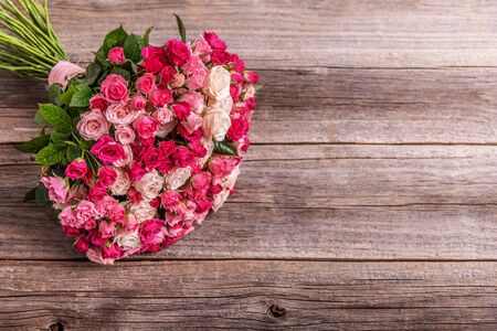 A bouquet of roses on a wooden background. Stock Photo - 132121521