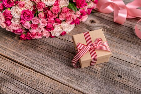 Roses and a gift on a wooden background
