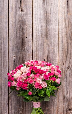 A bouquet of roses on a wooden background.