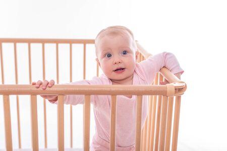 Babymädchen am Laufstall.