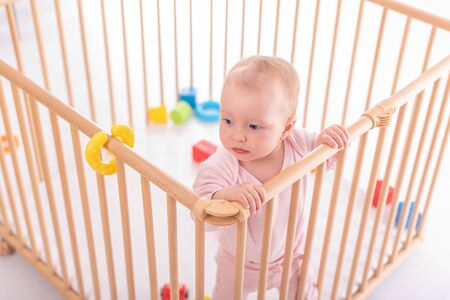 Baby girl at childrens playpen. Banque d'images