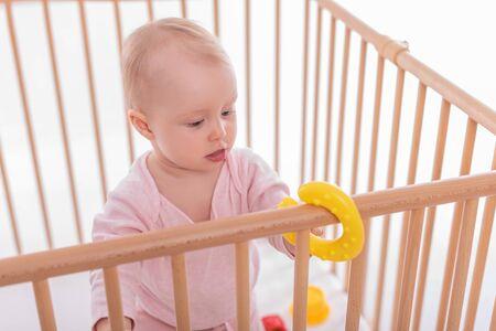 Babymeisje bij kinderbox. Stockfoto