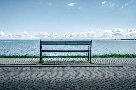 Bench on the shore of a lake or a sea. Stockfoto