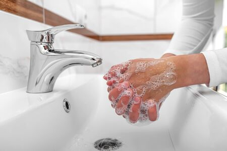 Someone washes hands with soap while standing in the bathroom. Archivio Fotografico