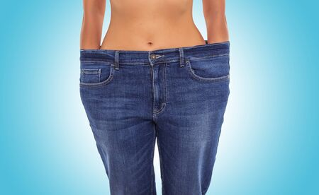 Slender girl in big jeans on a blue background. Losing weight. Фото со стока