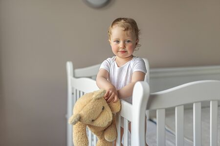 Cheerful little girl playing with a teddy bear in a good mood.