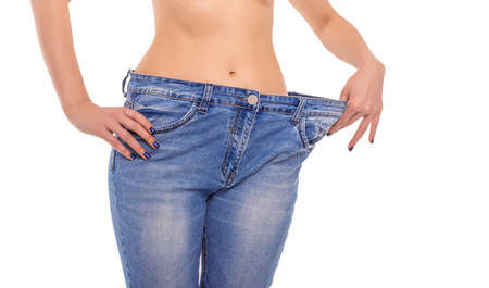 Slender girl in big jeans on a white background. Losing weight.