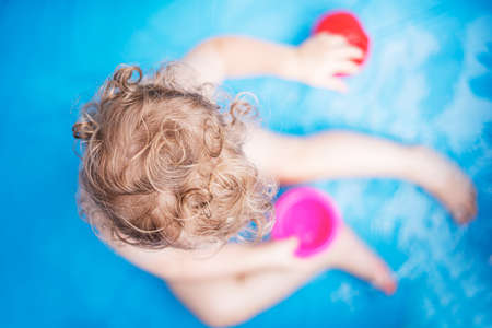 Child girl bathes in a bathtub or pool with toys.