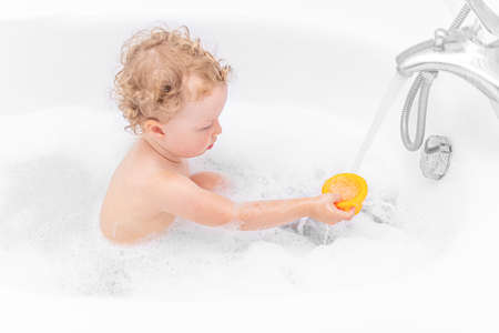 A child girl bathes in a bath.