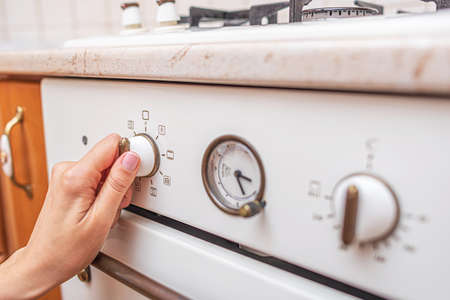 Woman uses the oven at home in the kitchen.