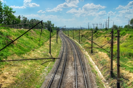 The railway leaving afar. the background of green grass and blue cloudy sky. Stock Photo