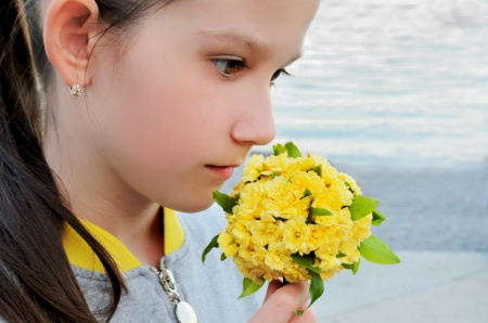 A beautiful girl smells bouquet yellow flowers on a background of the sea. portrait in profile close-up.