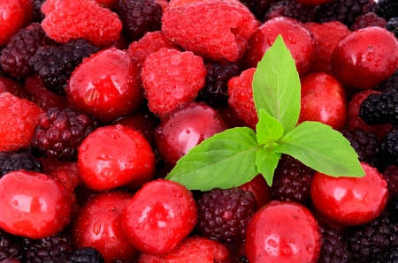 cherry, raspberry, blackberry on full background close-up, decorated with green leaves Stock Photo