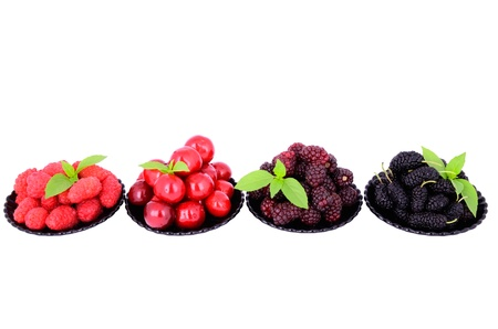 mulberry, cherry, raspberry, blackberry in a plates isolated on white, decorated with green leaves Stock Photo