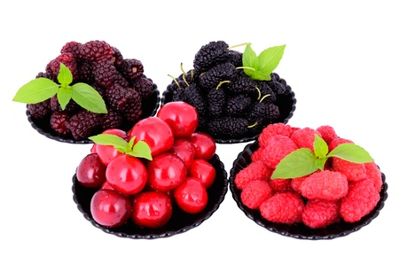 mulberry; cherry; raspberry; blackberry in a plates close-up isolated on white; decorated with green leaves