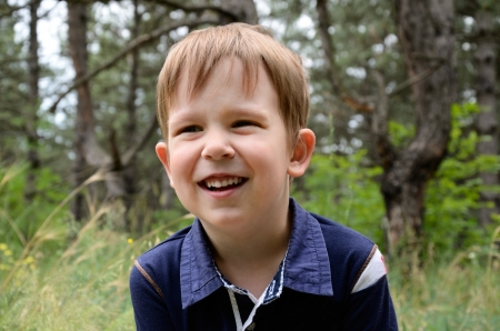 European laughing boy 4-5 years. Close-up on a background of grass and trees Stock Photo