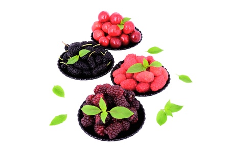 mulberry; cherry; raspberry; blackberry in a plates close-up isolated on white; decorated with green leaves.