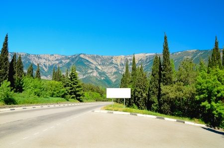 The road disappearing into the distance among the firs and cypresses. Crimean mountains in Ukraine. Space for text.