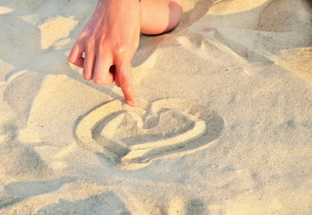 Heart symbol drawn in the sand  finger girl drawing a heart in the sand