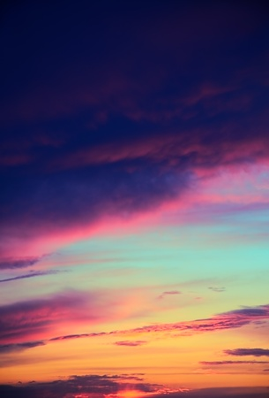 blue, aquamarine, red, orange, yellow, purple, gray clouds in the blue sky during sunset  vertical